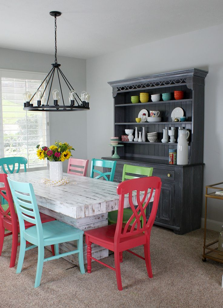 To give the room a color boost, this blogger painted eight wooden chairs lively shades of pink, blue, green and red.