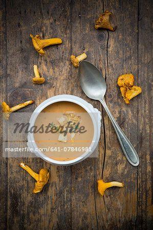 Soup bowl of cream of chanterelle soup, spoon and chanterelles on dark wood  – Bild © Masterfile.com: Kreative Stock-Fotografie, Vektoren und Illustrationen für Internet-, Print- und Mobile-Nutzung