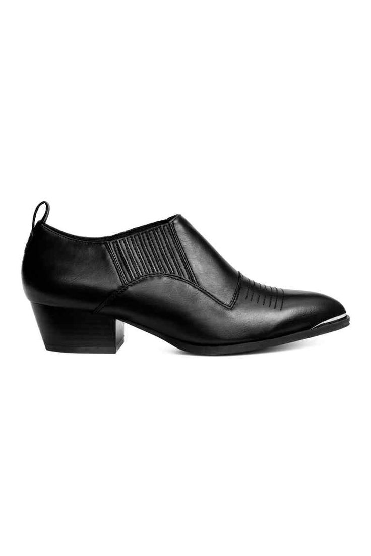 Boots: Hoge schoenen van imitatieleer met sierstiksels vooraan. De schoenen hebben een spitse neus met metalen versteviging, een schuine hak en bekleed elastiek opzij. Een satijnen voering en binnenzool en een rubberen buitenzool. Hak 4 cm.
