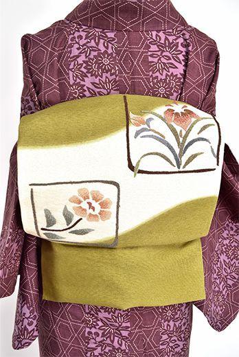 象牙色とうぐいす色の、たゆたう霞のようなやわらかな染め分けに、相良刺繍を思わせる細やかな玉を連ねたような味わいのある刺繍であらわされた花模様が豊かな詩情をさそう名古屋帯です。