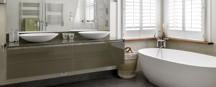 Bespoke modern floating double vanity unit with large mirror - bespoke fitted bathroom furniture by Brayer. Modern bathroom design in period home with freestanding bath and classic style plantation shutters.