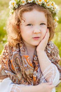 Кучерявая девочка в платке и венке из ромашек