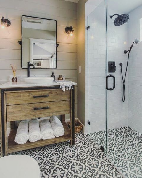 a big wood counter unit with rustic dark fixtures and a beautiful black and white mosaic tile in the bathroom.