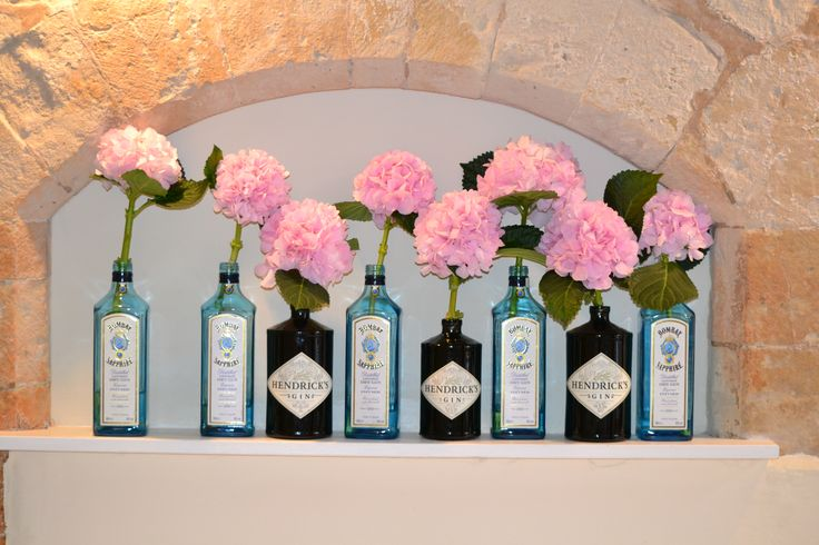 Bombay Sapphire and Hendrick's Gin Bottles filled with pale pink Hydrangea stems at Farnham Castle Weddings