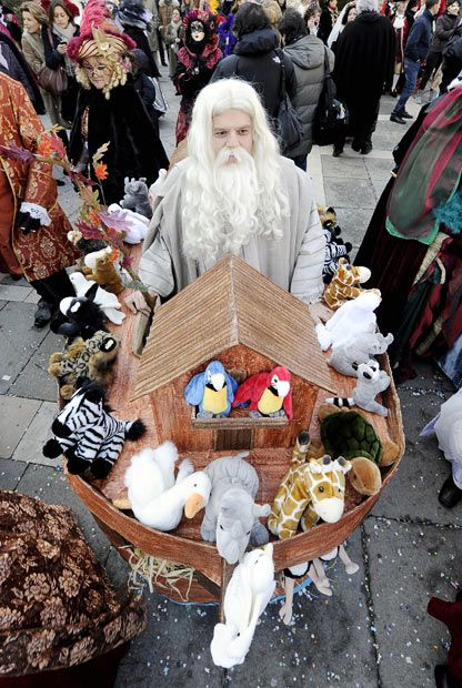 A carnival-goer dressed in a costume representing Noah and his ark poses for a picture