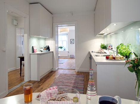 Tässä kodissa on valkoiset seinät, valkoiset kaapit, sileitä pintoja. Niinon monessa muussakin kodissa jaideahan on, että siihen ei kyllästy. Valkoisena pienikin keittiö näyttää avaralta ja sileät pinnat on helppo pitää puhtaana. Kaappien väliseen seinään löytyy jo muutakin pinnoitetta kuin kaakelit, mintun vihreä lasi ontyylikäs ratkaisu ja helposti puhdistettavissa. Kun lattiapinta on näyttävä, ei ruokapöydän alla tarvita mattoa, mikä helpottaa siivousta huomattavasti. Näin kauniisti…