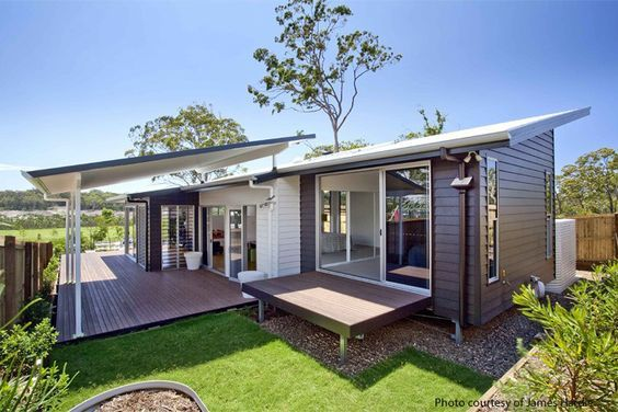 Weatherboard home with flyover skillion roof covering entertainment area:
