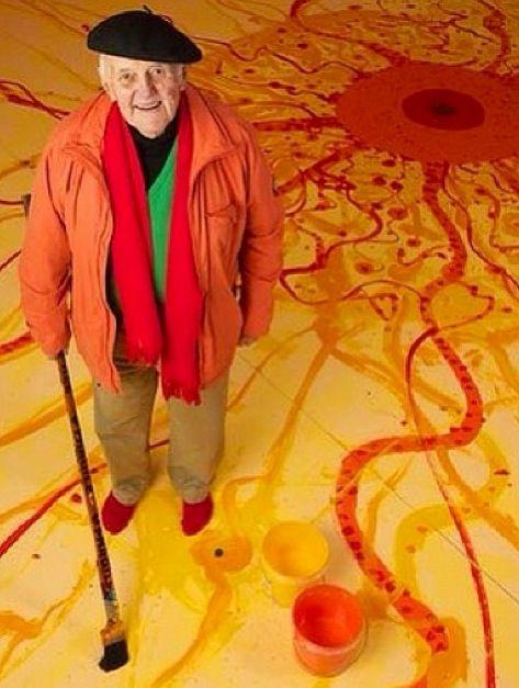 """John Olsen painting """"King Sun"""" on the floor of his studio"""
