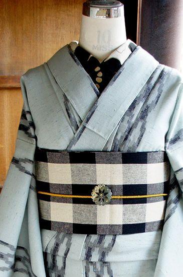 薄曇りの空のような、水色を帯びた明るいグレーの地に、鎖のようなよろけ縞が織り出されたモダンなウールの単着物です。