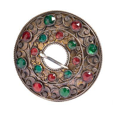 Sølje   Sølv og forgylt sølv.   Filigran med røde og grønne glassstener. Bergen 1884 DIAMETER 7,5