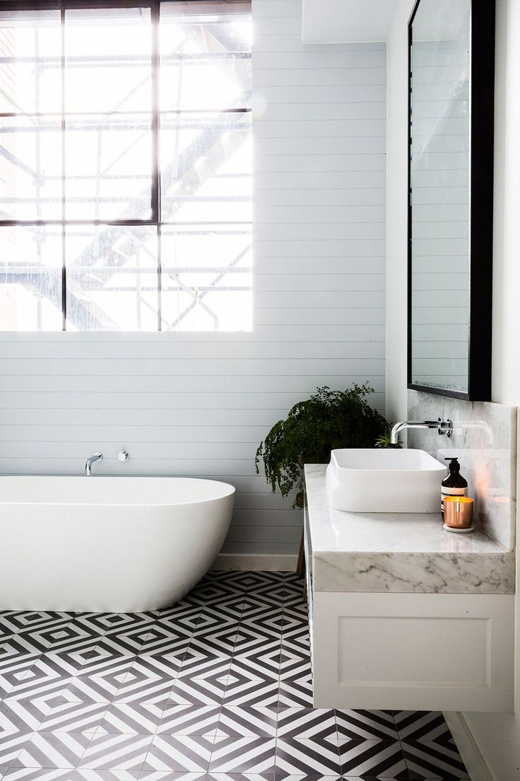Amazing graphic floor tiles in this bathroom, with a beautiful marble bench top sink and freestanding bathtub.