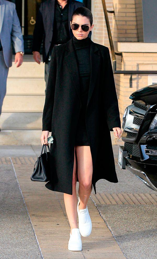 Kendall Jenner usa turtleneck com mini saia e casaco sobretudo, ambos pretos, e finaliza o look com tênis branco
