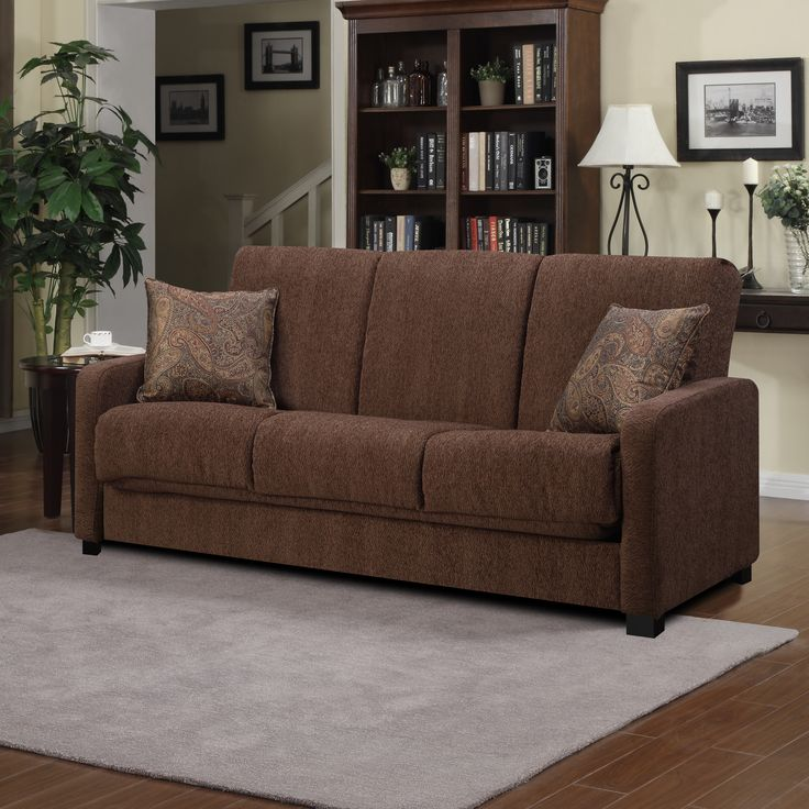 Comfortable and stylish, the transitional convert-a-couch features squared arms and converts into a full size bed with the touch of a hand. The futon sleeper sofa is covered in a durable brown fabric and works well in any decor.