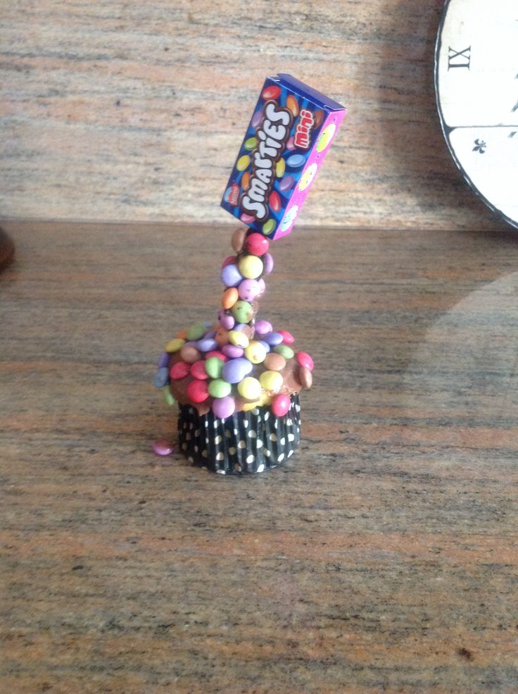 Gravity cupcake .use the mini boxes of smarties .coat stick in chocolate use more melted chocolate to stick on the smarties