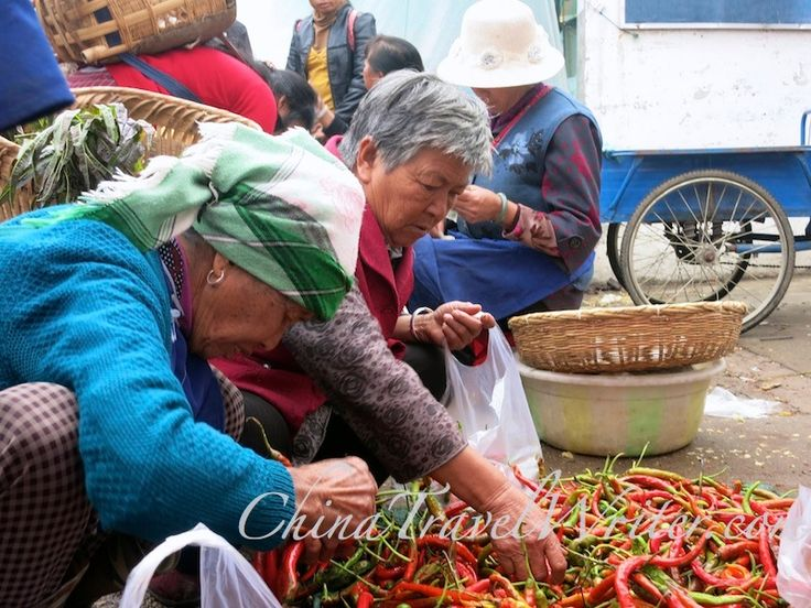 Women shopping for peppers at a market.