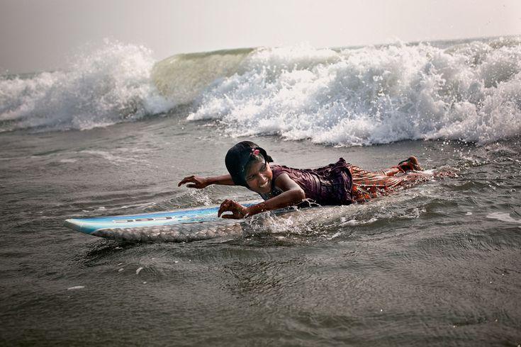 Un surfeur local entraîne un groupe de filles qui travaillent à la plage pour…