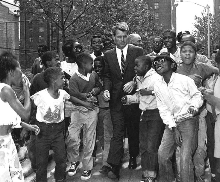 Attorney General Robert Kennedy walks down a street in New York, surrounded by children. He is visiting a summer reading program in Harlem.