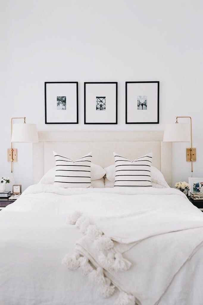 Beautiful Scandinavian style bedroom with black and white striped pillows and pom pom throw