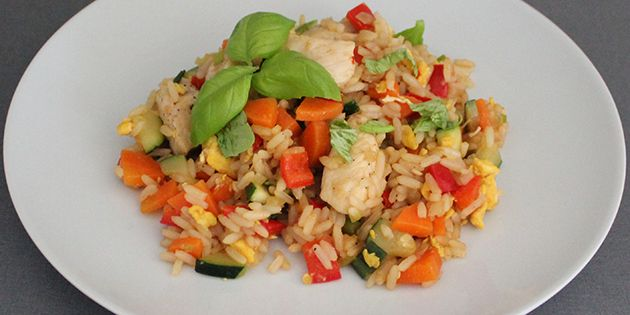 Stegte ris med æg og kylling pyntet med frisk basilikum.