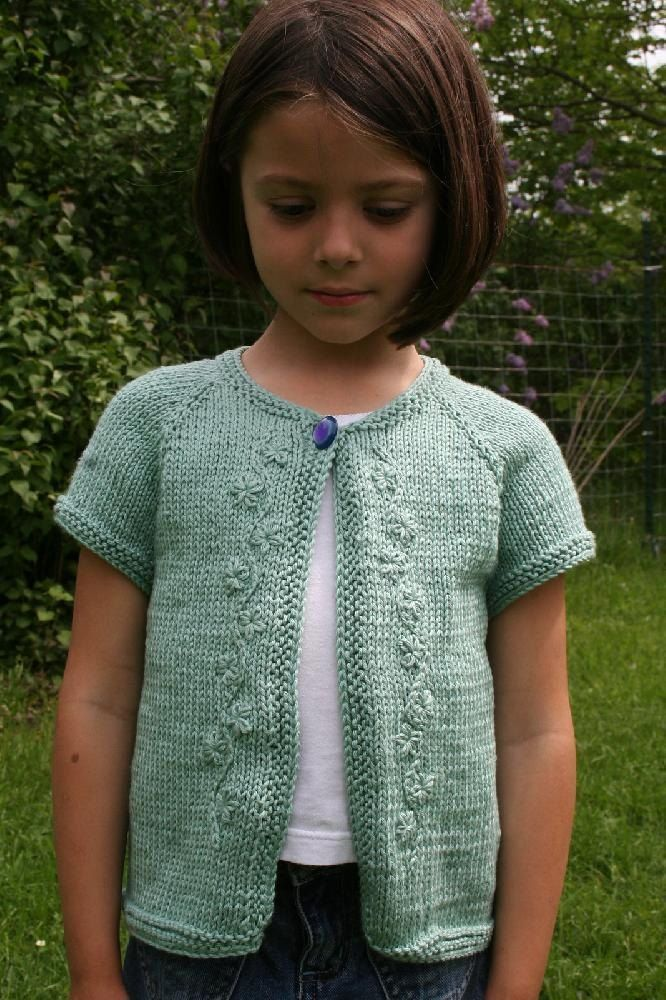 Knitted from the top down, this little cardigan does not have any seams and the finishing is minimal. Cap sleeves and a garter stitch border compliment the simple, yet attractive design. The embroidery, which gave this design it's title, is optional; instructions are given in the text.Thank you Ilse Althierr for the beautiful embroidery.