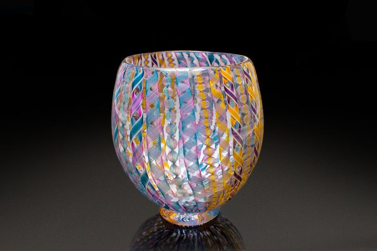 Mardis Gras Zanfirico Vase by April Wagner. This beautiful hand-blown glass vessel features zanfirico, the product of a traditional Venetian glassblowing technique that uses thin, handmade multicolored rods of glass called cane, which are lined up, fused together, and then encased in molten glass working from a 2000 degree furnace. The custom cane color patterns in this piece are one of a kind.