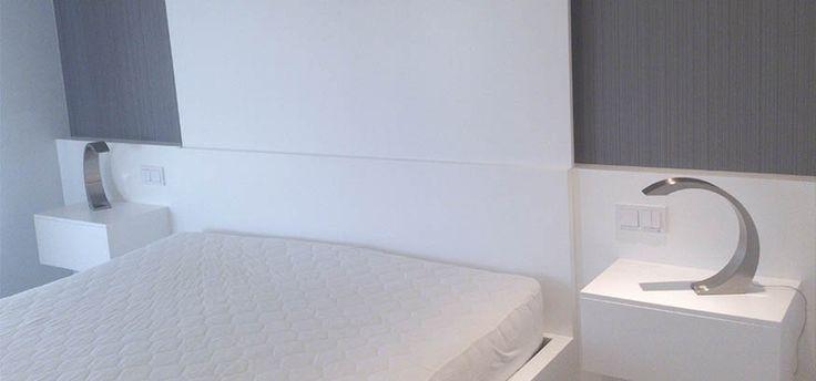 Cabecero, mesillas y canapé lacados en blanco.
