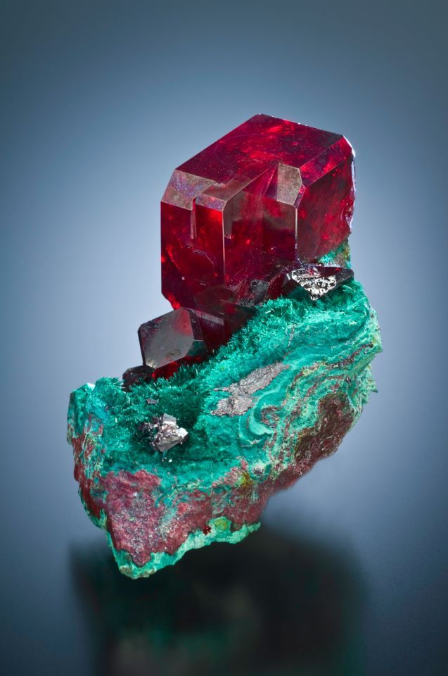 Cuprite, a copper mineral that was not known until 1845, is a secondary mineral of oxidizing sulfide-rich copper deposits. It's symmetry is in the Isometric system, but this specimen looks to have unequal axes of symmetry. This slightly more than one inch crystal is from Bisbee, Arizona.