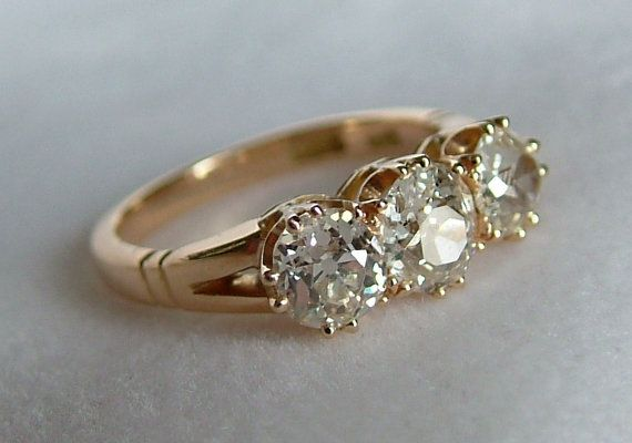 This stunning antique 18ct yellow gold diamond trilogy engagement ring holds three beautiful sparkling white old mine cut diamonds totaling
