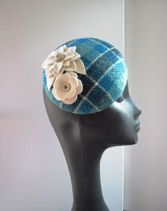 Cocktail hat in a gorgeous vintage teal tweed. The base is hand blocked buckram and wire, covered with a beautiful turquoise, teal ,dark ocean blue, and cream hand loomed vintage wool tweed fabric. This fabric is just stunning! The way the multi-color yarns were twisted before weaving makes the fabric almost appear to sparkle. It is topped off with two ivory fur felt flowers. The hat attatches with an elastic. Lined with ivory kimono silk.  My high quality cocktail hats are made with great…