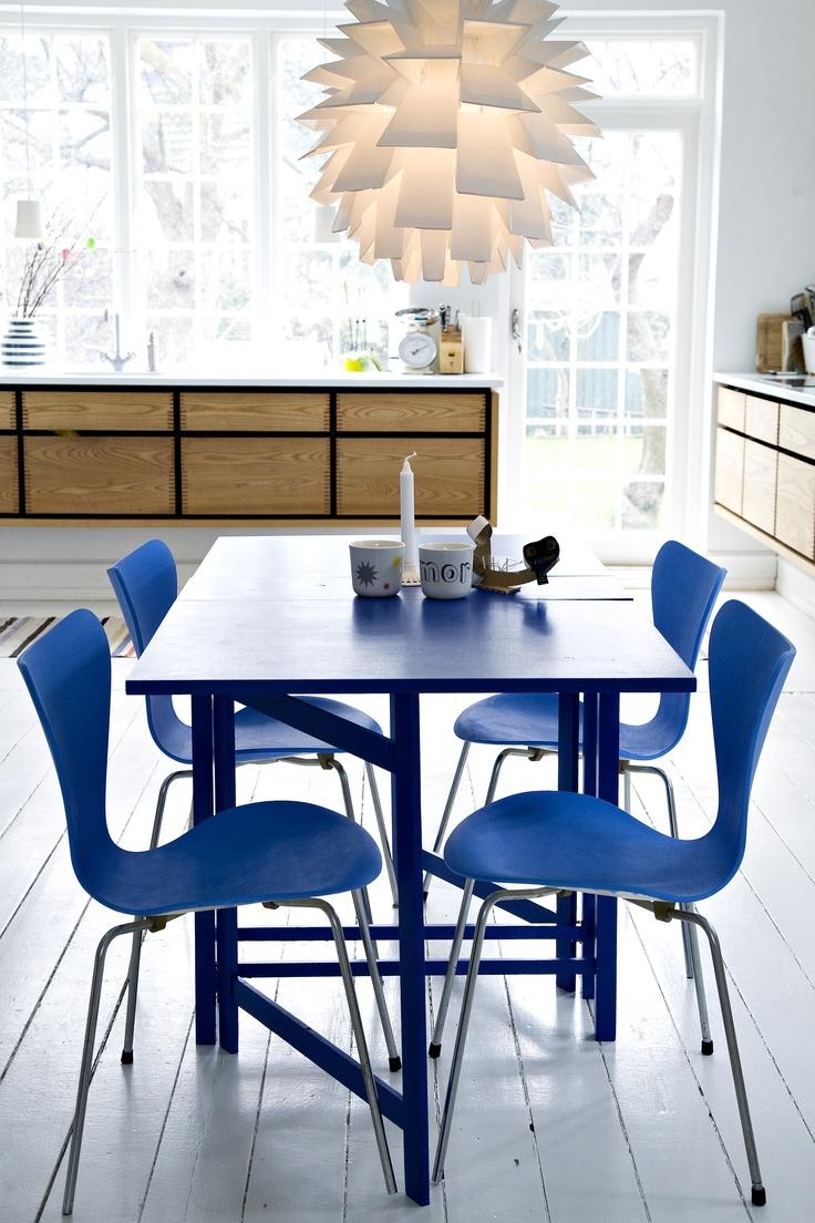A luminária Norm69, da Normann Copenhagen,  marca presença nesta contemporânea sala de jantar.