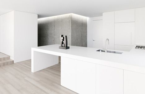 The simple lines and clean nature of this kitchen are complimented superbly by the washed out tones of the timber flooring and texture, tone  pattern are all added through the raw concrete panels at the rear of the space; this is further supplemented by the use of a lighting trough above the wall which adds a lightness to the wall whilst adding to the existing shadow and texture across the walls surface.