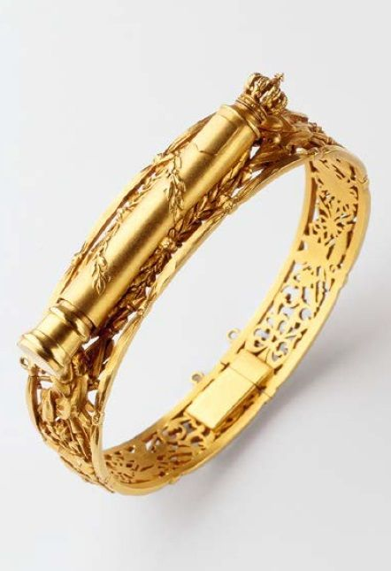 Joseph Chaumet - An antique gold pencil holder bracelet, circa 1890. Central motif depicting a marshal's baton encircled by laurels and surmounted by the Bourbon crown, originates in carved gold military trophies. This bracelet presents the motif within a wreath of ribbons and bows. It was commissioned as a wedding gift to mark a marriage between the House of Orléans and industrial dynasty Schneider.