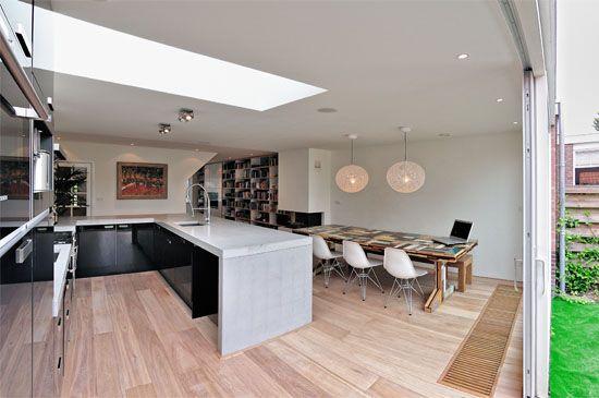 Verbouwing met uitbouw te Amstelveen. Uitbouw met daklicht. Zwarte keuken met betonnen aanrechtblad.