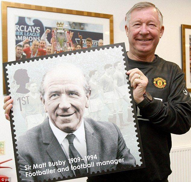 Ferguson poses with a blown up First Class stamp featuring Sir Matt Busby