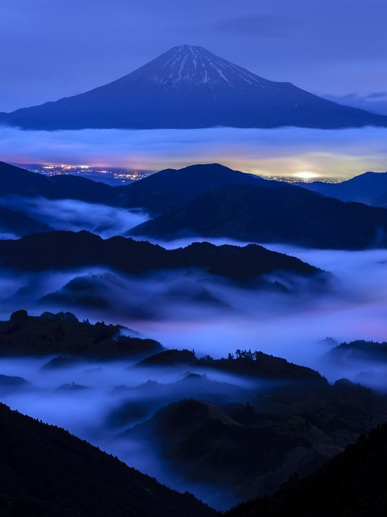 Mt Fuji, Japan. Before dawn. The beautiful harmony of night view appeared. The cloud was colored beautifully by the lights under the sea of clouds.
