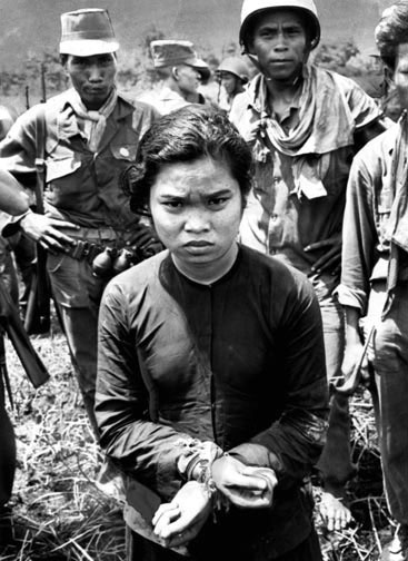 Al Chang. Stars and Stripes  South Vietnam, 1962. Her hands bound by a Viet Cong flag, a Vietnamese girl is guarded by soldiers after being captured in the Mekong Delta.