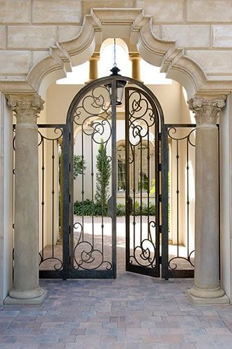 "A ""Statement"" entry: Elegant iron gates in a sculptured cast stone arch."