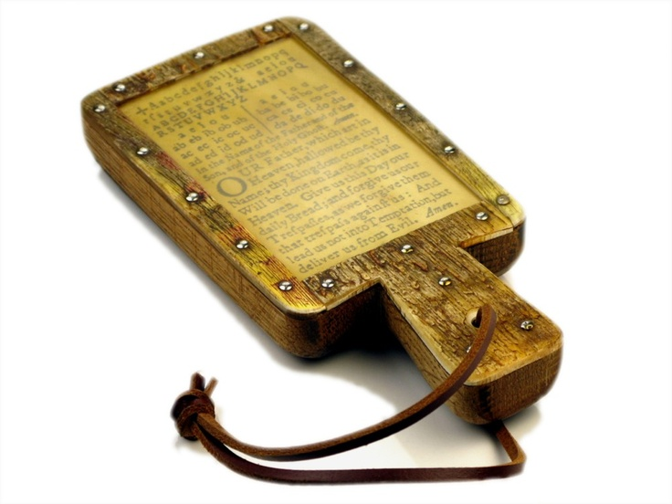 """Horn books were widely used by children from the 15th-18th century. These """"books"""" were often made of wood covered with a printed alphabet page. A very fine, transparent slice of a cow's horn was nailed over the page to preserve the paper, making horn books a practical and sturdy tool. Many horn books also included the Lord's Prayer."""