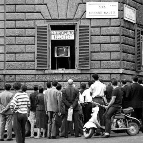 Passanti che guardano le olimpiadi da un televisore di una casa Roma 1960