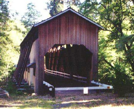 """The rustic, well-known covered bridge spanning the Applegate River, just eight miles from the California border, was built in 1917 by contractor Jason Hartman and his son Wesley on land donated by Aldelbert """"Deb"""" McKee."""