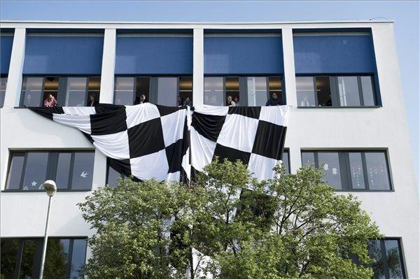Pedagógusok egy nagyméretű kockás zászlót engednek le a Budaörsi Herman Ottó Általános Iskola ablakaiból a pedagógusok egész napos, országos sztrájkjának napján, 2016. április 20-án. MTI Fotó: Koszticsák Szilárd