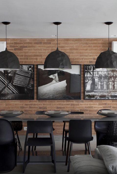 Para a sala de jantar, o arquiteto Marcelo Rosset escolheu cinco diferentes modelos de cadeiras, todas na cor preta. Os pendentes Rock, sobre a mesa (Micasa), são uma criação da Diesel em parceria com a italiana Foscarini. Na parede de tijolos estão os quadros do artista Rodrigo Petrella, em preto e branco