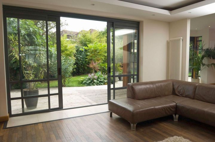 modern sliding glass door designs for living room with wooden floor and brown L shaped sofa