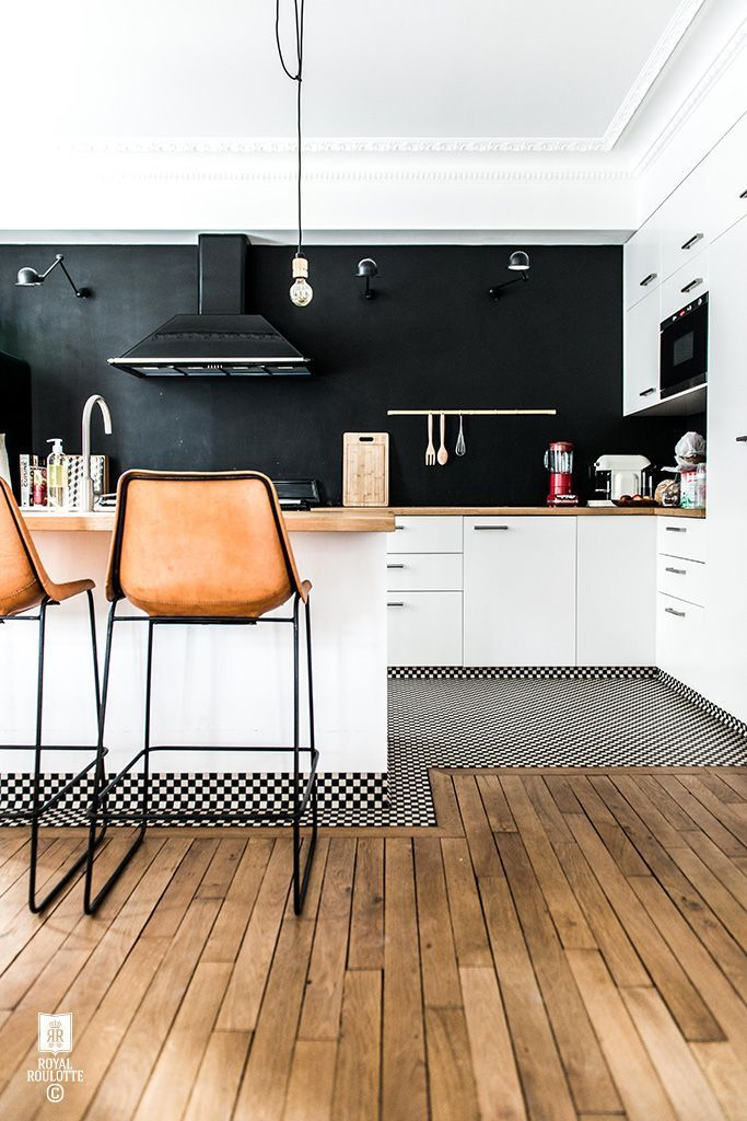 A black-and-white kitchen with leather bar stools.