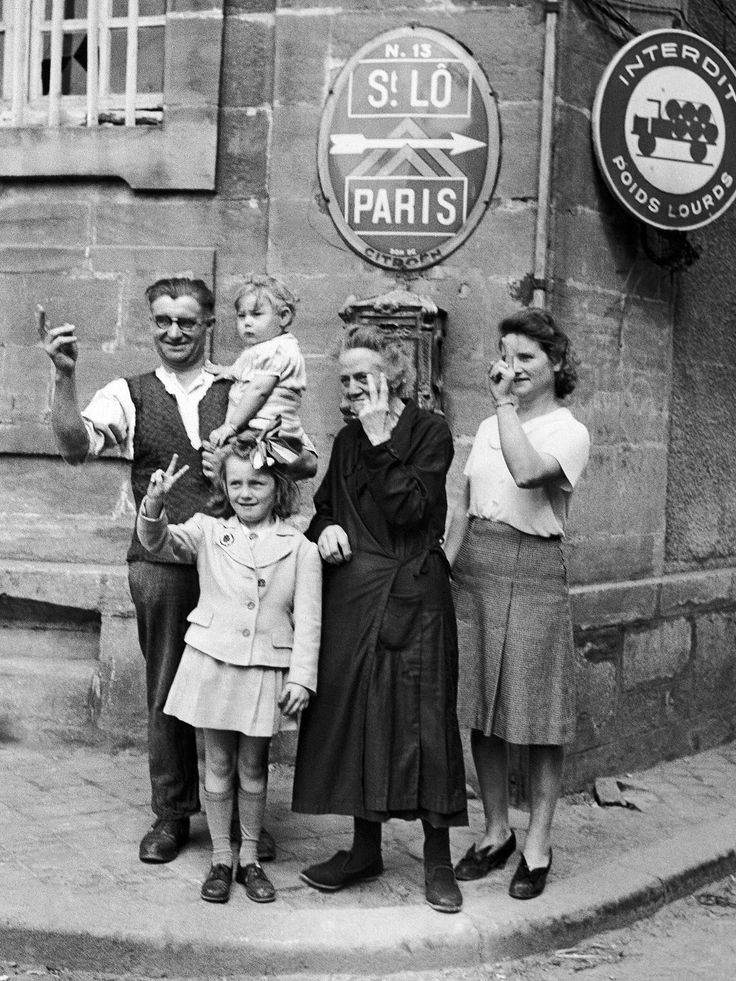 French civilians on the outskirts of St. Lo on July 25, 1944, cheer on allied troops with the V for victory signs.  Associated Press