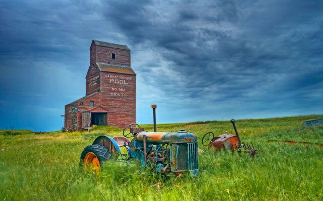 A grain elevator and tractors on the prairie near Bents, Saskatchewan country-magazine.com