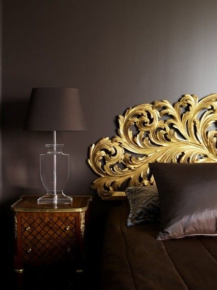 Satiny brown wall and an absolutely stunning baroque style golden headboard. Love the colors together and the acrylic table lamps is the perfect addition. A lovely seamlessly luxurious baroque bedroom!