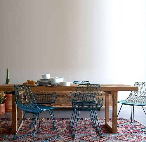 Southwestern modern. Blue metal chairs, wood table, colorful geometric rug.