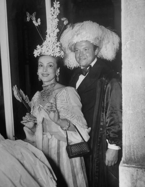 "{Le Bal du Siècle} Orson Welles and Mademoiselle de Heeren - Christian Dior's costume was designed by Salvador Dalí, the old Aga Khan was a ""sinister looking figure in blak silk"" and Orson Welles was in black tie with his head suitably topped with feathers as his costume was late."
