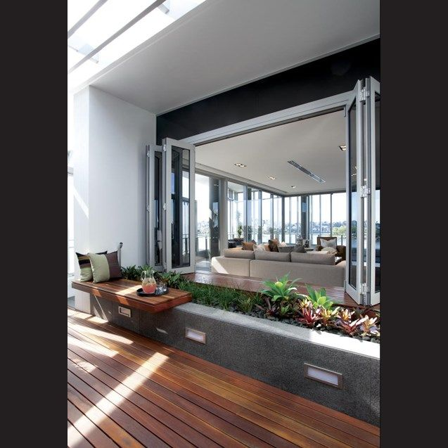 Deep bifolding windows open up the interior to a balcony that wraps around two sides of the penthouse. Timber decking and window ledges add visual warmth.